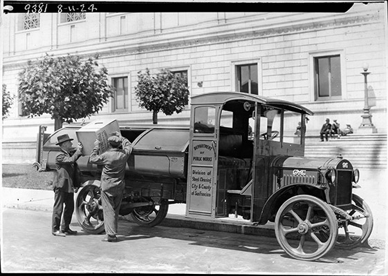 Two men dumping waste into the back of an old early 20th century Street Cleaning truck in front of San Francisco City Hall.