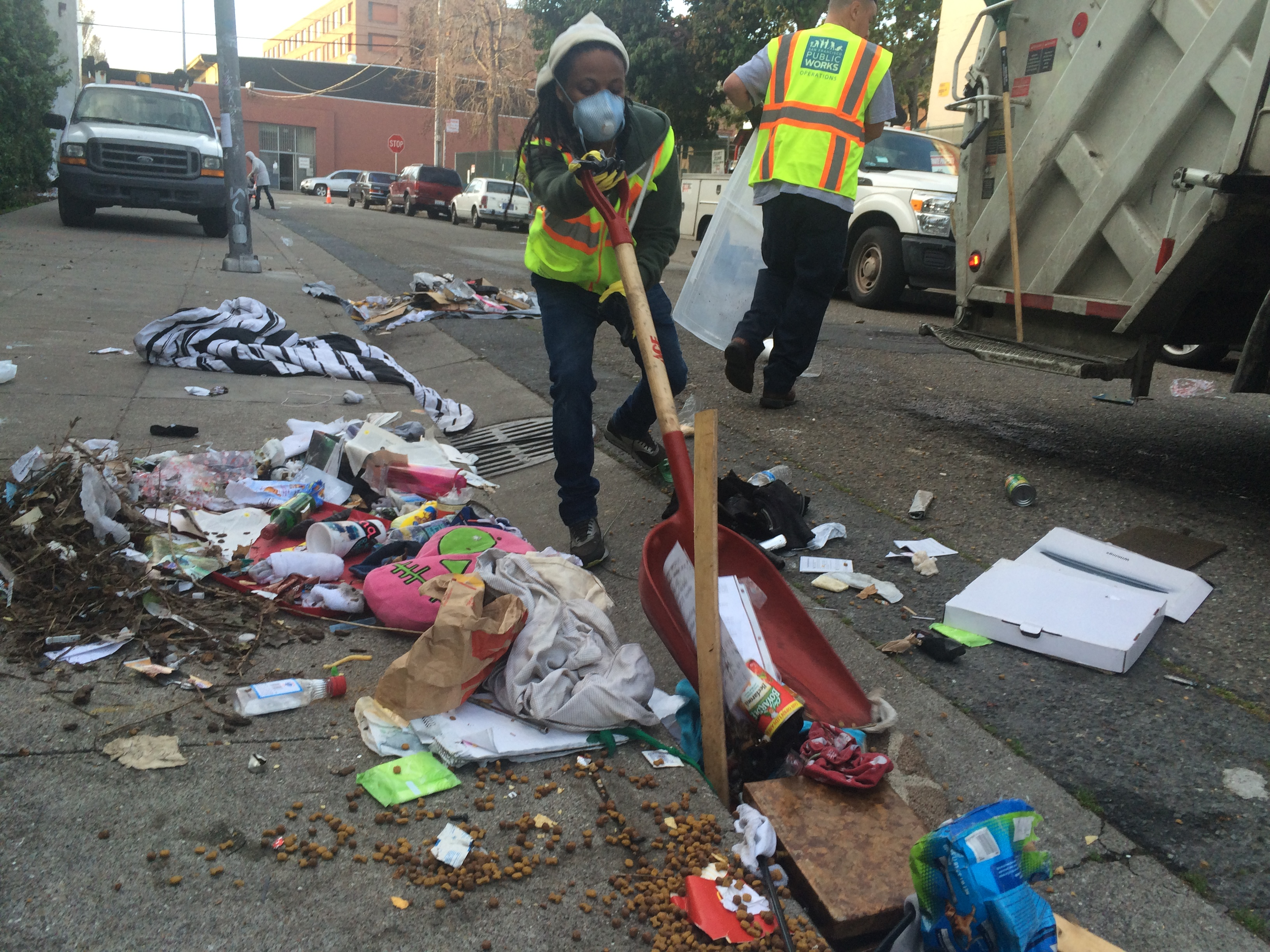 Worker cleaning litter-strewn street