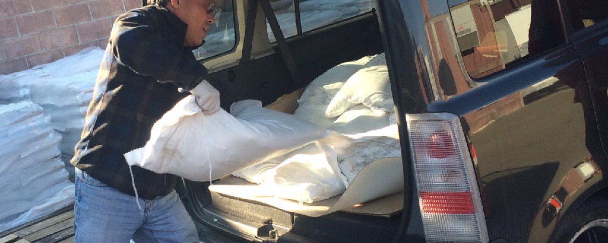Man loading sandbags into his car